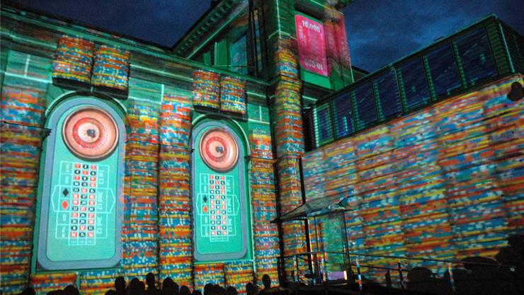 Die Zuschauer bestaunen die Lichtinstallation des Frankfurter Künstlers Martin Böttcher an der Casino-Fassade.