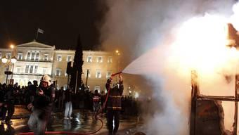 Feuerwehrmänner löschen ein brennendes Billetthäuschen vor dem Parlament Athens