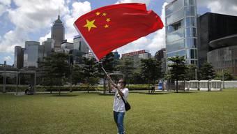 Ein Pro-China-Aktivist bejubelt mit der Staatsflagge das neue Sicherheitsgesetz für Hongkong. Die Börsen jubeln mit.