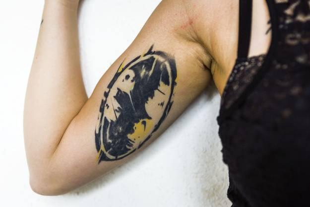 Am inneren rechten Oberarm trägt sie Batman