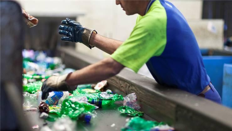 Hellblaue, weisse, grüne und braune Flaschen: Ein Angestellter in der Sortieranlage in Frauenfeld TG hat alle Hände voll zu tun. Gaetan Bally/Keystone