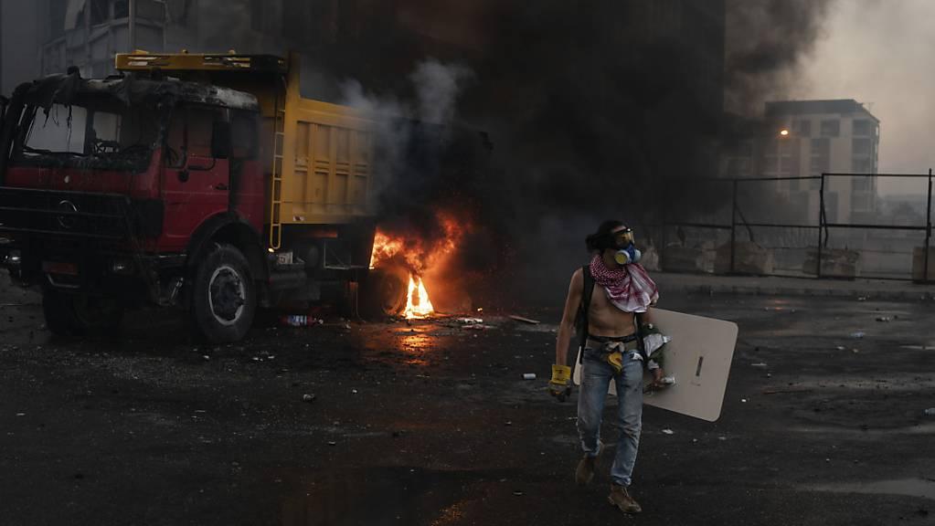 Ein Demonstrant mit Atemmaske und Schutzschild steht vor einem brennenden Lastwagen. Foto: Felipe Dana/AP/dpa