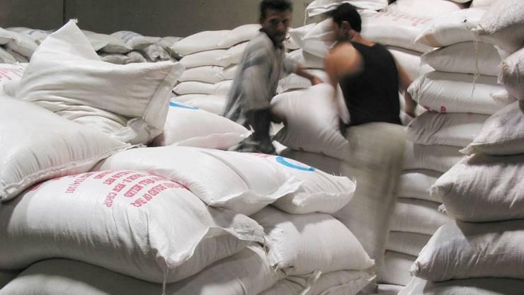Männer stapeln Hilfsgüter im Irak (Symbolbild)