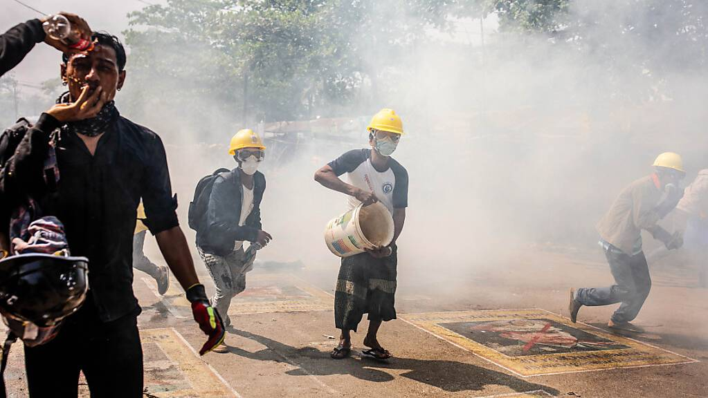 Gegner der Militärjunta von Myanmar laufen bei einem Protest gegen die Junta über die Straße und kippen Wasser auf rauchende Tränengaskanister. Die neue Junta in Myanmar geht weiter mit brutaler Gewalt und Inhaftierungen gegen politische Gegner, Demonstranten und Journalisten vor. Foto: Aung Kyaw Htet/SOPA Images via ZUMA Wire/dpa