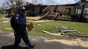 Ein Polizist geht in Tully Heads bei der Bestandesaufnahme von Haus zu Haus
