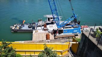 Für die Sanierung der Ufermauer unterhalb des Gartens der Alten Universität wird ein Seilbagger benutzt, der auf einem Ponton im Rhein schwimmt.
