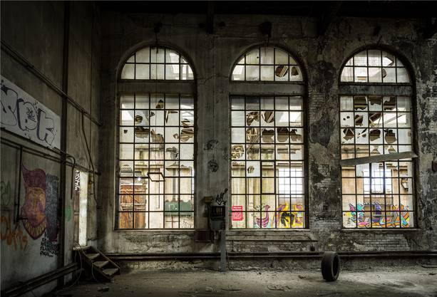 Die Fabrik von innen. Staub und Schutt liegen am Boden.