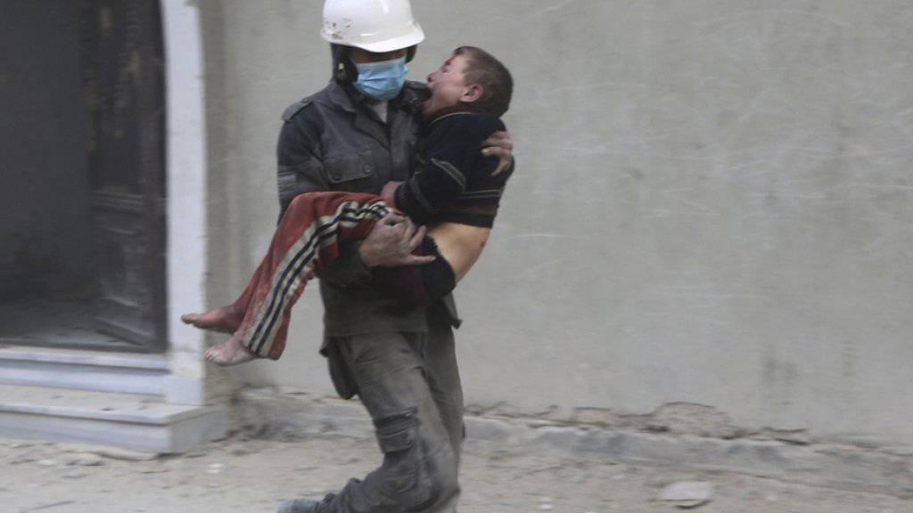 Ein Zivilschützer, ein sogenannter Weisshelm, trägt einen bei Angriffen der syrischen Armee verwundeten Knaben in Ost-Ghuta nahe Damaskus.