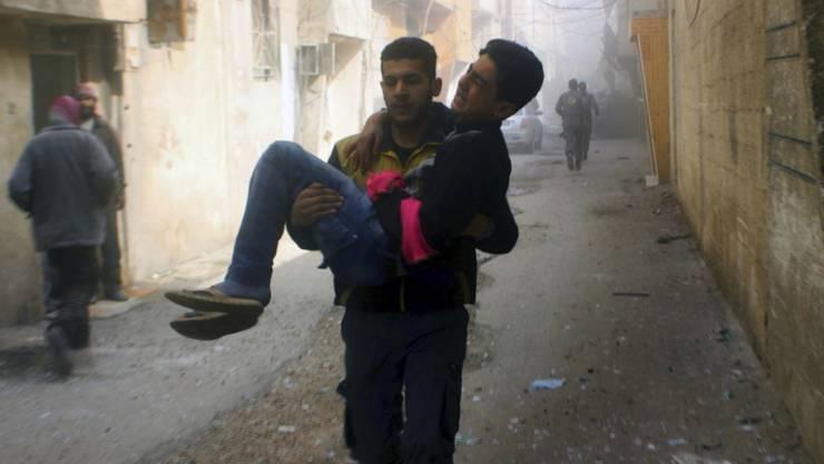 Helfer trägt in Ost-Ghuta einen bei einem Angriff verwundeten Mann