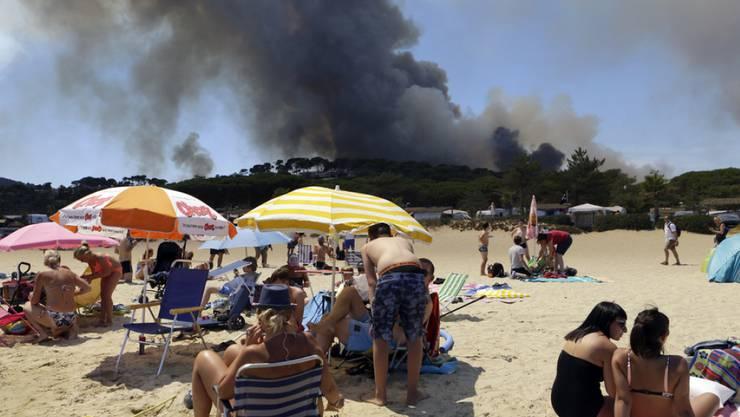 Menschen am Strand von Le Lavandou an der französischen Riviera - im Hintergrund steigen schwarze Rauchwolken in den Himmel. Wegen den Waldbränden in Südfrankreich mussten bereits 10'000 Menschen evakuiert werden.