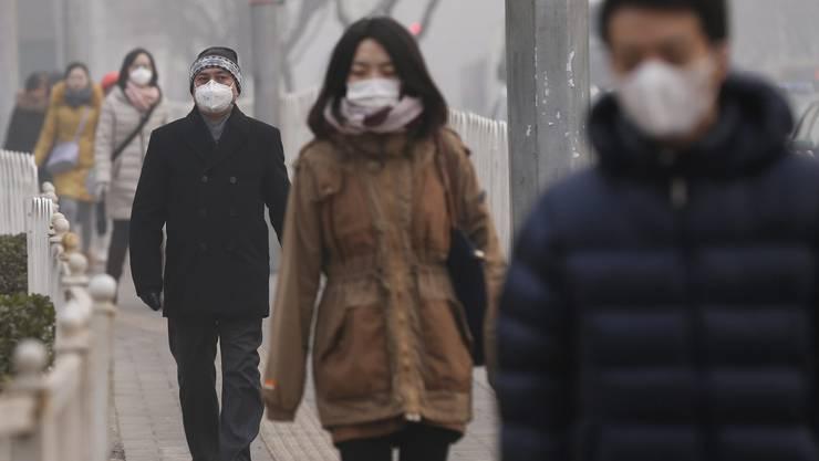 Viele Chinesen tragen wie von der Regierung empfohlen draussen Atemschutzmasken.