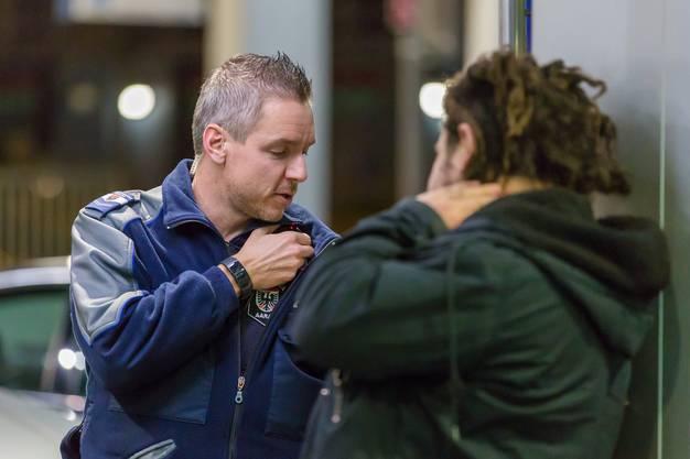 """Die Polizisten halten Ausschau nach """"Altbekannten"""" und nach Personen, die sich auffällig verhalten. Hier hat Roman Weiss gerade den Ausweis des Mannes kontrolliert und funkt nun Personalien an die Zentrale. Diese prüft, ob eventuell eine Fahndung oder Wegweisung besteht."""