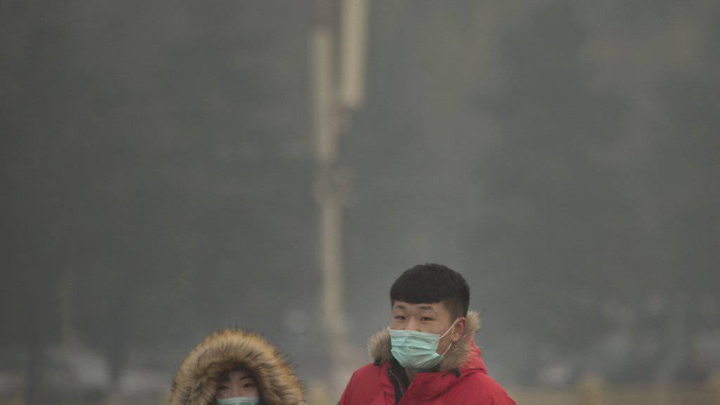 Menschen schützen sich sich mit Gesichtsmasken gegen den Smog am Samstag in Peking.