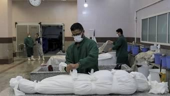 dpatopbilder - Ein Mitarbeiter bereitet den Leichnam eines Mannes vor, der an den Folgen einer Corona-Infektion gestorben ist, in einem Leichenschauhaus auf dem Friedhof Behesht-e-Zahra am Rande der iranischen Hauptstadt. Der Friedhof ist einer der weltweit größten  mit 1,6 Millionen Menschen, die auf seinem mehr als 5 Quadratkilometer großen Gelände beerdigt sind. Foto: Ebrahim Noroozi/AP/dpa