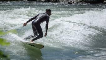Ein Surfer auf der Flusswelle in der Reuss in Bremgarten.