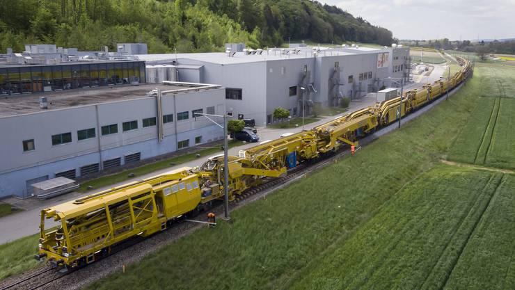 Der Bauzug auf der Strecke zwischen Büren und Lyss, im Hintergrund die Firma Bigler