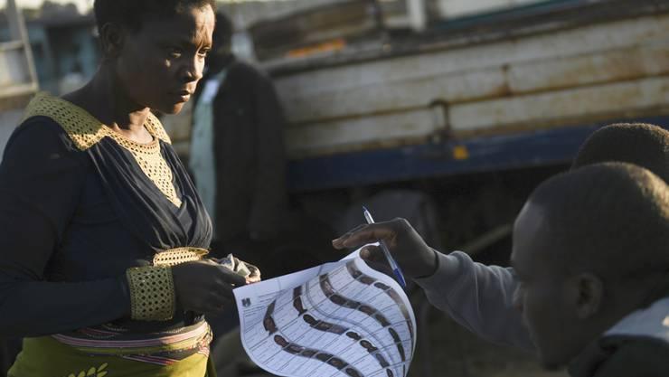Eine Wählerin erhält ihren Stimmzettel für die erneuten Präsidentschaftswahl in Malawi. Foto: Thoko Chikondi/AP/dpa