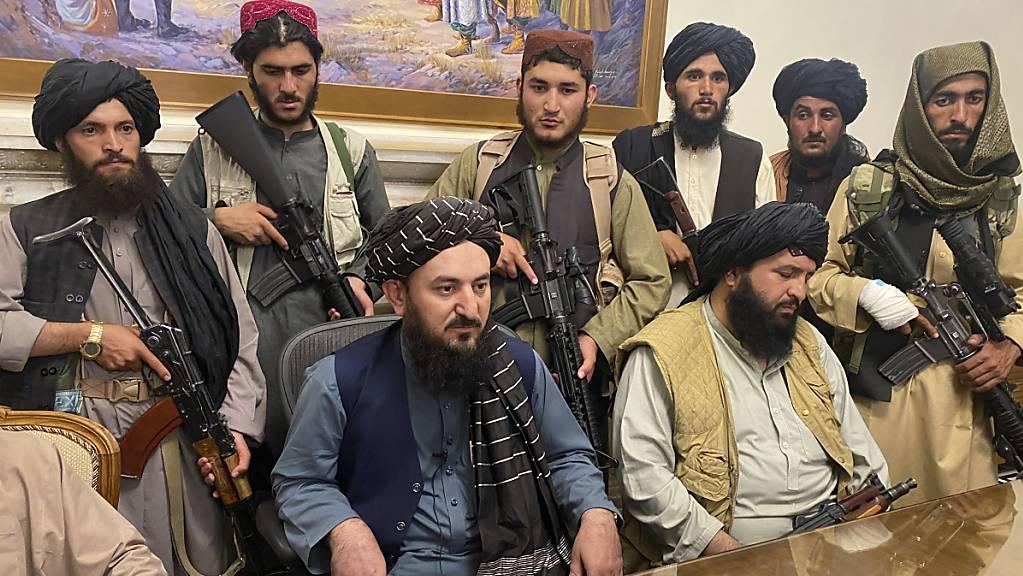 Taliban-Kämpfer sitzen in einem Raum des Präsidentenpalastes. Foto: AP/dpa