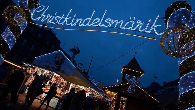 """ARCHIV - Das Wort """"Christkindelsmärik"""" prangt in großen beleuchteten Buchstaben an einem Zugang zum Weihnachtsmarkt. Foto: Marijan Murat/dpa"""