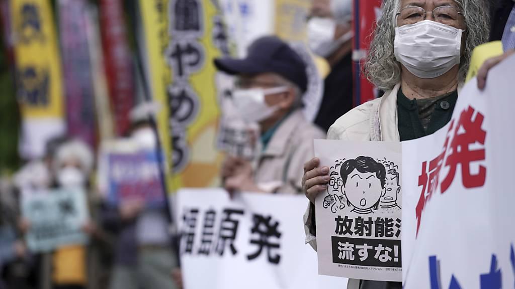 Menschen skandieren während einer Kundgebung vor dem Büro des Premierministers Suga Slogans. Japan will das im havarierten Atomkraftwerk Fukushima angesammelte radioaktive Wasser nach einer Behandlung trotz des örtlichen Widerstands und der Bedenken von Nachbarländern ins Meer leiten. Foto: Eugene Hoshiko/AP/dpa
