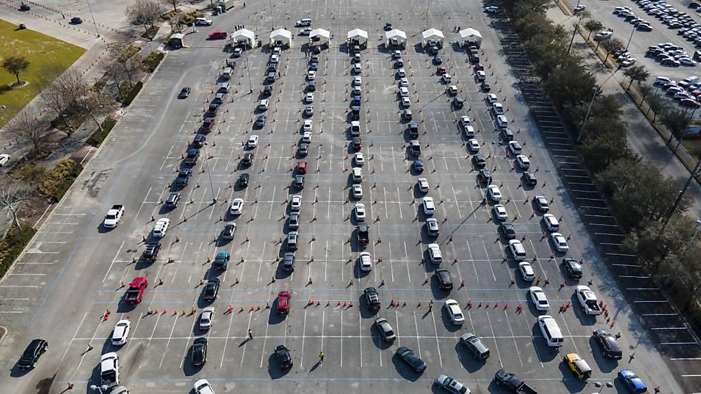 ARCHIV - Autos stehen auf einem Parkplatz in Houston Schlange - die Insaßen warten darauf, gegen das Coronavirus geimpft zu werden. Foto: Mark Mulligan/Houston Chronicle/AP/dpa - ACHTUNG: Nur zur redaktionellen Verwendung und nur mit vollständiger Nennung des vorstehenden Credits