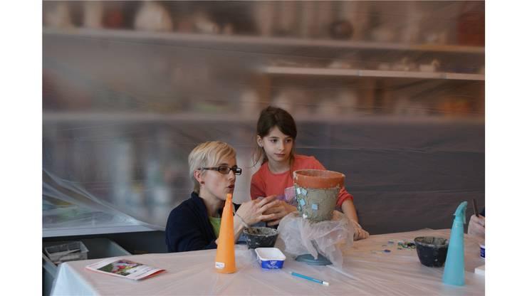 Claudia Zumbühl hilft Alba beim Auftragen des Blumentopf-Mosaiks.