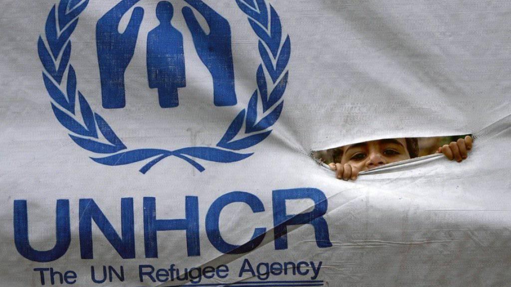Ein Flüchtlingskind schaut durch ein UNHCR-Transparent. (Symbolbild)