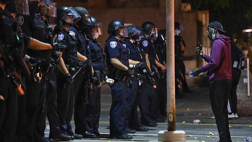 Ein Demonstrant steht während einer Demonstration vor Polizisten. Nachdem ein 41-jähriger Afroamerikaner infolge eines brutalen Polizeieinsatzes verstarb, wurden sieben Beamte vom Dienst suspendiert. Foto: Adrian Kraus/AP/dpa