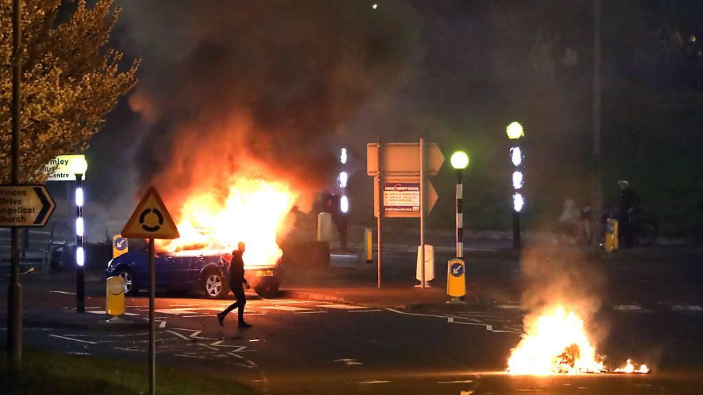 Ein Mann geht an einem brennenden Auto vorbei. Bei Protesten im nordirischen Belfast sind mehrere Polizisten verletzt worden. Foto: Peter Morrison/PA Wire/dpa