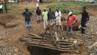 Minenarbeiter an einer der Eingänge, die überflutet wurden und offenbar dutzende illegal arbeitende Goldschürfer das Leben gekostet hat.