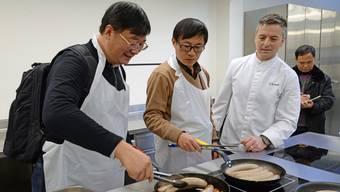 20 Chinesische Bildungsmanager bereiten Bratwurst und Rösti zu