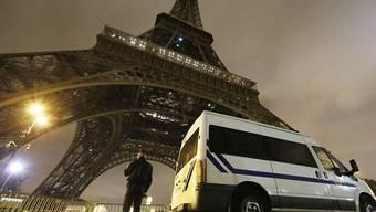 Ein Polizist steht Wache beim Eiffelturm in Paris.