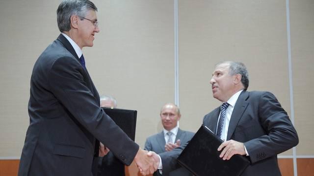 Unter den Augen von Wladimir Putin (M.) geben sich ExxonMobil-Entwickllungschef Neil Duffin und Rosneft-Chef Eduard Chudajnatow die Hand