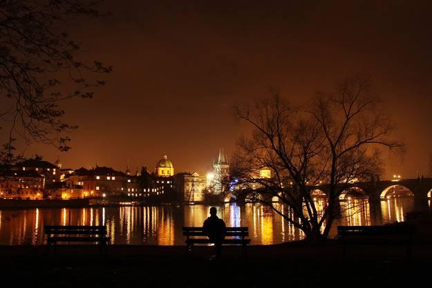 Vom Ufer der Moldau aus erstrahlt Tschechiens Hauptstadt Prag nachts in Gold.