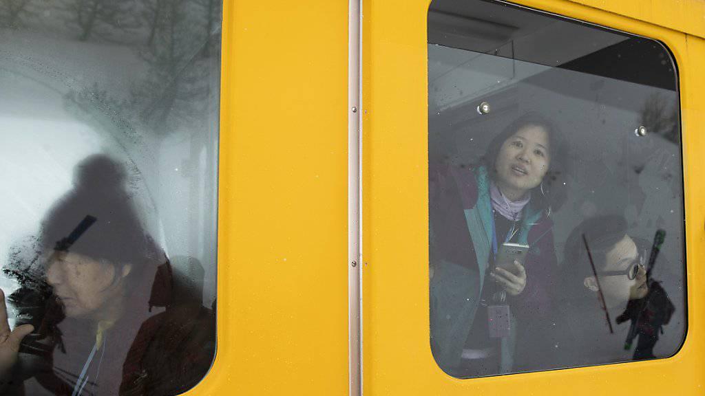 Asiatische Touristen schauen aus einem stillstehenden Zug der Wengernalpbahn im Berner Oberland. Das «Touristen-GA» blieb auch 2018 ein Renner. (Archivbild)