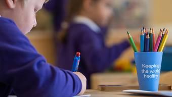 ARCHIV - Ein Schüler sitzt an einem Tisch in einem Klassenzimmer der Grundschule «Queen's Hill Primary School», vor ihm steht ein Stiftebecher mit der Aufschrift «Keeping the world healthy». Foto: Joe Giddens/PA Wire/dpa