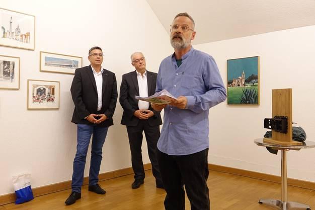 Kurator Rudolf Velhagen bei seiner Vernissagenrede - flankiert vom Badener Stadtammann Markus Schneider (l.) und dem Wettinger Gemeindeammann Roland Kuster.