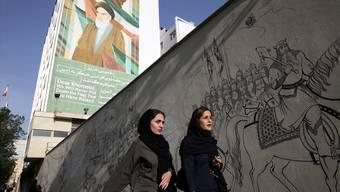 Zwei Iranerinnen in Teheran. Im Hintergrund: Ayatollah Khomeini.