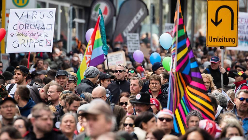 Protestler nehmen an einer Demonstration der Initiative «Querdenken» teil und ziehen mit Ziel Cannstatter Wasen durch die Stuttgarter Innenstadt. Foto: Christoph Schmidt/dpa