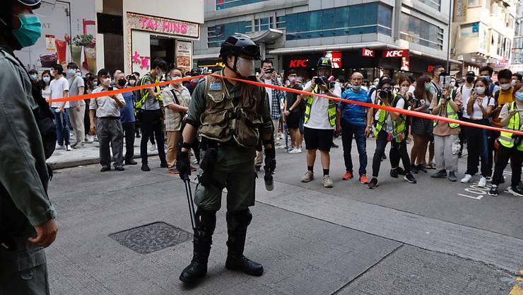 Die Bereitschaftspolizei hält im Hongkonger Central District Wache, um die dort versammelten Demonstranten fernzuhalten. Die Hongkonger Polizei ist vor dem Parlamentskomplex in Bereitschaft, wo heute in einer Parlamentssitzung über ein umstrittenes Gesetz gegen den Missbrauch der chinesischen Nationalhymne debattiert wird. Foto: Kin Cheung/AP/dpa