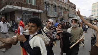 Jemenitische Demonstranten tragen einen Verwundeten davon