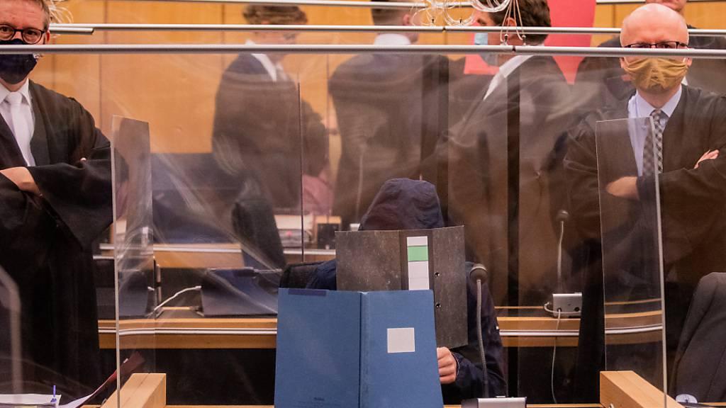 ARCHIV - Der damals 27-Jährige Hauptangeklagte (vorne), seine Mutter (ganz hinten links) und ein dritter Angeklagter (roter Hefter) sitzen im Gerichtssaal. Im Missbrauchskomplex von Münster soll der Hauptangeklagte wegen schweren sexuellen Missbrauchs von Kindern in 29 Fällen für 14 Jahre ins Gefängnis. Foto: Rolf Vennenbernd/dpa-Pool/dpa