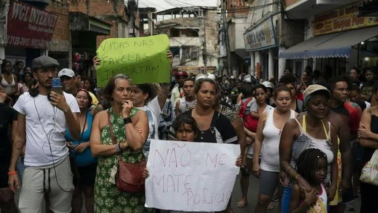 """Nach der Tötung eines Mädchens durch einen Militärpolizisten demonstrieren hunderte Menschen in Rio de Janeiro gegen Polizeigewalt. Ein Kind hält ein Schild mit der Aufschrift """"Töte mich nicht, Polizei""""."""