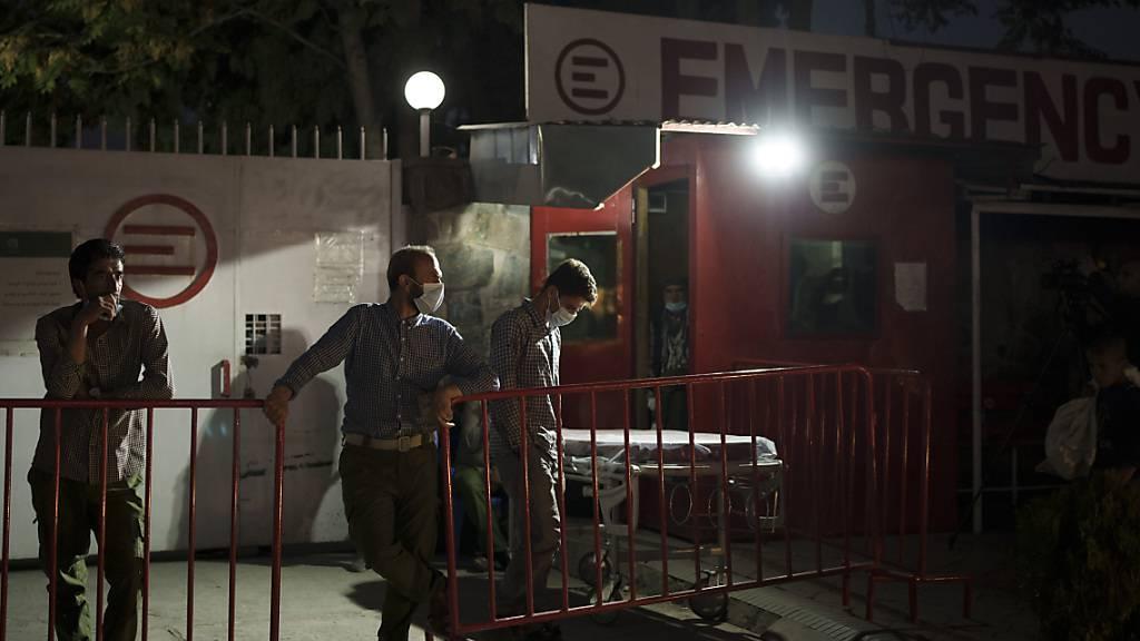Arbeiter warten nach einer Explosion an der Eidgah-Moschee vor dem Emergency NGO Krankenhaus. Foto: Felipe Dana/AP/dpa