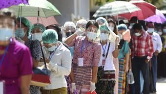dpatopbilder - Wähler die Mund-Nasen-Schutz und Schutz-Visiere tragen stehen Schlange vor einem Wahllokal, zur Stimmabgabe für die Parlamentswahl. Bei der Parlamentswahl in Myanmar geht De-facto-Regierungschefin Aung als klare Favoritin für eine weitere Amtszeit ins Rennen. Foto: Thein Zaw/AP/dpa