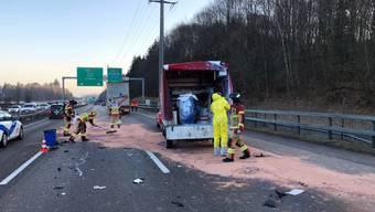 Feuerwehrleute beim Binden von flüssigem Kautschuk, das eines der verunfallten Fahrzeuge geladen hatte.