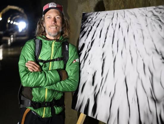 Der Fotograf David Carlier im Tälligrat neben einem seiner Bilder.