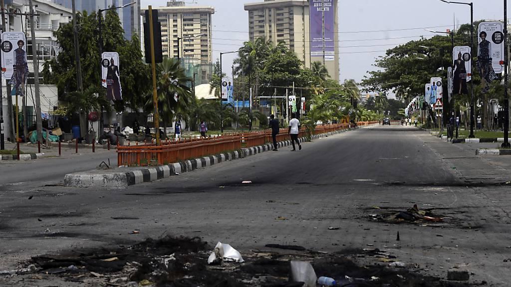 Auf einer sonst leeren Straße liegen die Überreste von abgebrannten Straßenblockaden. Nach einem Blutbad bei einer Kundgebung gegen Polizeiübergriffe gehen die Proteste im westafrikanischen Nigeria unvermindert weiter. Foto: Sunday Alamba/AP/dpa