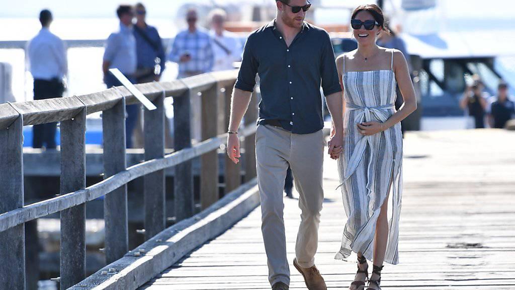Entspannt spazieren Prinz Harry und seine Frau Meghan über eine Mole auf Fraser Island zu einem Treffen mit Fans.