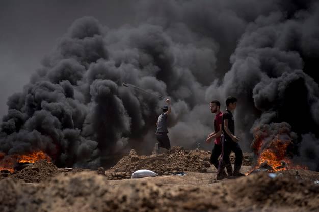Ein palästinensischer Demonstrant wirft Steine.